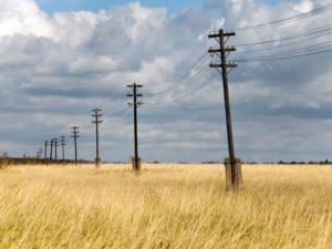 Линия деревянных колонн на бетонных основаниях с линиями низкого напряжения